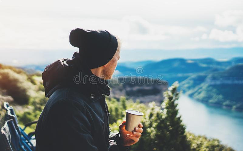 Hipster tourist hold in hands mug of hot drink, lonely guy enjoy sun flare mountain in auto, traveler drink cup of tea on nature. Vacation weekend concept on stock photography