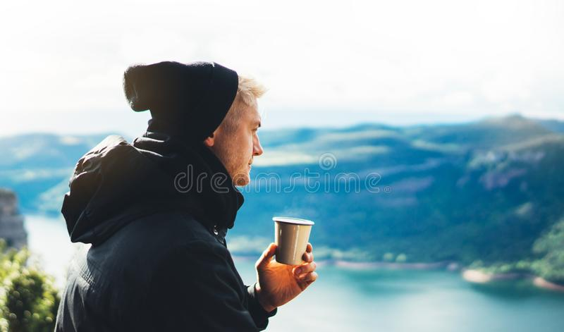 Hipster tourist hold in hands mug of hot drink, lonely guy enjoy sun flare mountain in auto, traveler drink cup of tea on nature. Vacation weekend concept on stock photos