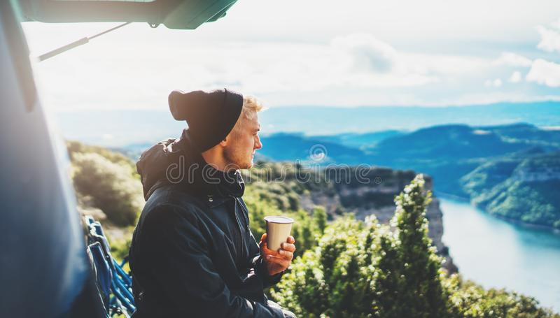 Hipster tourist hold in hands mug of hot drink, lonely guy enjoy sun flare mountain in auto, traveler drink cup of tea on nature. Vacation weekend concept on stock image