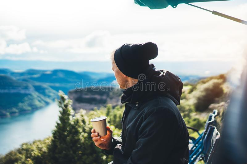 Hipster tourist hold in hands mug of hot drink, lonely guy enjoy sun flare mountain in auto, traveler drink cup of tea on nature. Vacation weekend concept on royalty free stock images