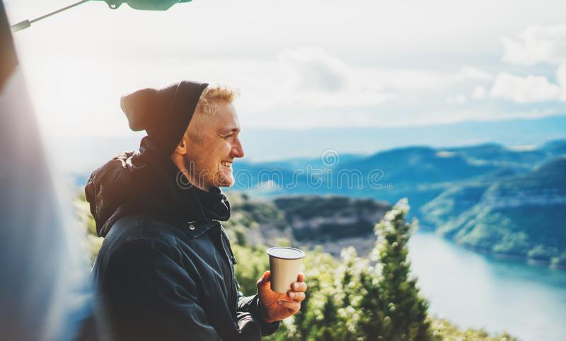 Hipster tourist hold in hands mug of hot drink, lonely guy smile enjoy sun flare mountain in auto, happy traveler drink cup of tea stock photo