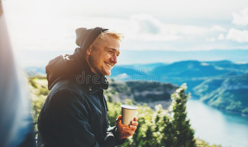 Hipster tourist hold in hands mug of hot drink, lonely guy smile enjoy sun flare mountain in auto, happy traveler drink cup of tea royalty free stock images