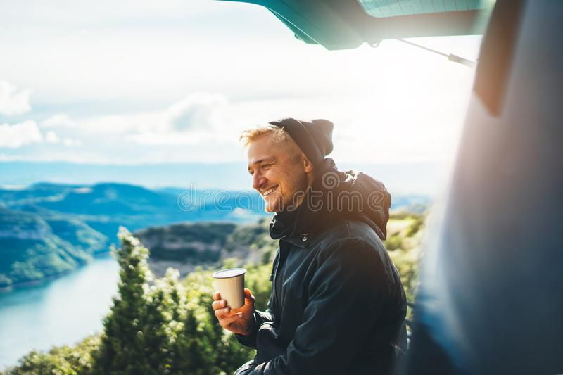 Hipster tourist hold in hands mug of hot drink, lonely guy smile enjoy sun flare mountain in auto, happy traveler drink cup of tea stock photography