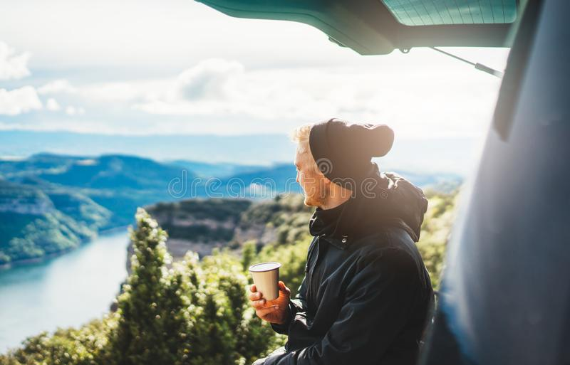 Hipster tourist hold in hands mug of hot drink, lonely smile guy enjoy sun flare mountain in auto, traveler drink cup of tea. On nature, vacation weekend royalty free stock photography