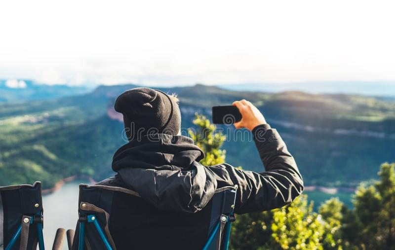 Hipster tourist hold in hands smartphone taking photography click on mobile camera, photographer looking on gadget technology. Panoramic landscape vacation royalty free stock photos