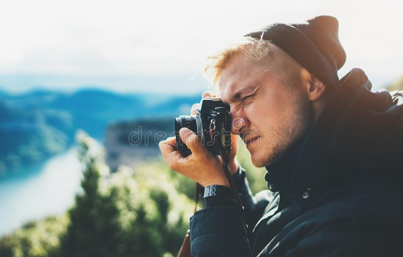 Hipster tourist hold in hands taking photography click on retro vintage photo camera in auto, photographer looking on camera stock images