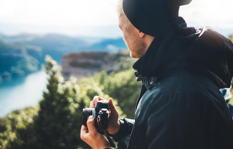Hipster tourist hold in hands taking photography click on retro vintage photo camera in auto, photographer looking on camera stock image