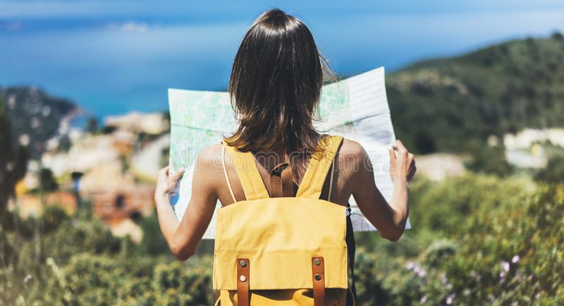 Hipster tourist hold and look map on trip, lifestyle concept adventure, traveler with backpack on background mountain and blue sea stock photos
