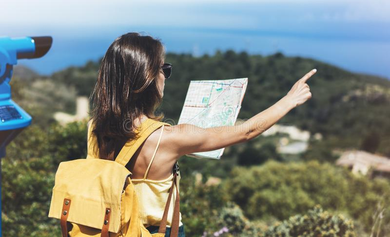 Hipster tourist hold and look map on trip, lifestyle concept adventure, traveler with backpack on background mountain and blue sea. Landscape horizon, young stock image