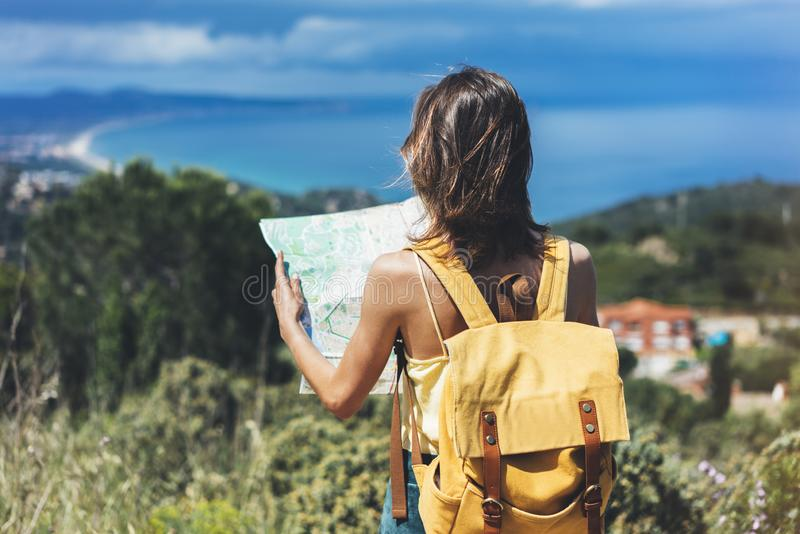 Hipster tourist hold and look map on trip, lifestyle concept adventure, traveler with backpack on background mountain and blue sea. Landscape horizon, young stock images