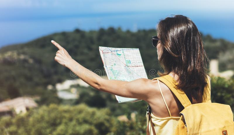 Hipster tourist hold and look map on trip, lifestyle concept adventure, traveler with backpack on background mountain and blue sea. Landscape horizon, young royalty free stock images