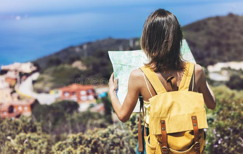 Hipster tourist hold and look map on trip, lifestyle concept adventure, traveler with backpack on background mountain and blue sea. Landscape horizon, young stock photography
