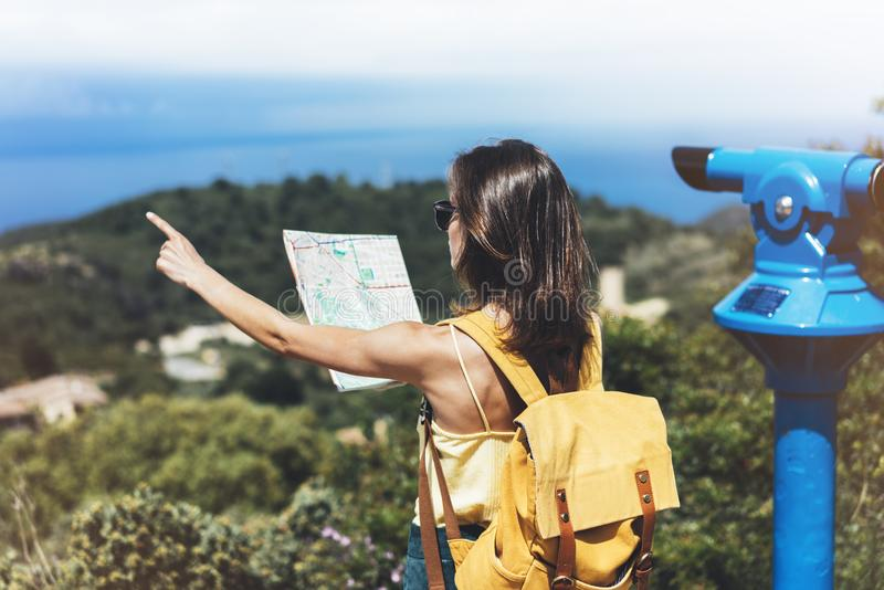Hipster tourist hold and look map on trip, lifestyle concept adventure, traveler with backpack on background mountain and blue sea. Landscape horizon, young stock photos