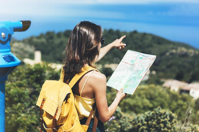 Hipster tourist hold and look map on trip, lifestyle concept adventure, traveler with backpack on background mountain and blue sea. Landscape horizon, young royalty free stock photos