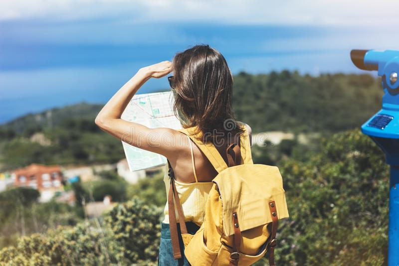 Hipster tourist hold and look map on trip, lifestyle concept adventure, traveler with backpack on background mountain and blue sea. Landscape horizon, young stock photo