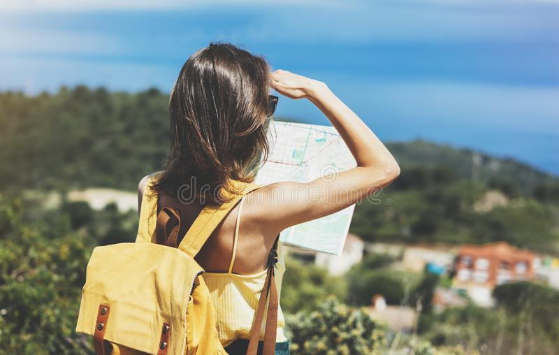 Hipster tourist hold and look map on trip, lifestyle concept adventure, traveler with backpack on background mountain and blue sea. Landscape horizon, young royalty free stock photography