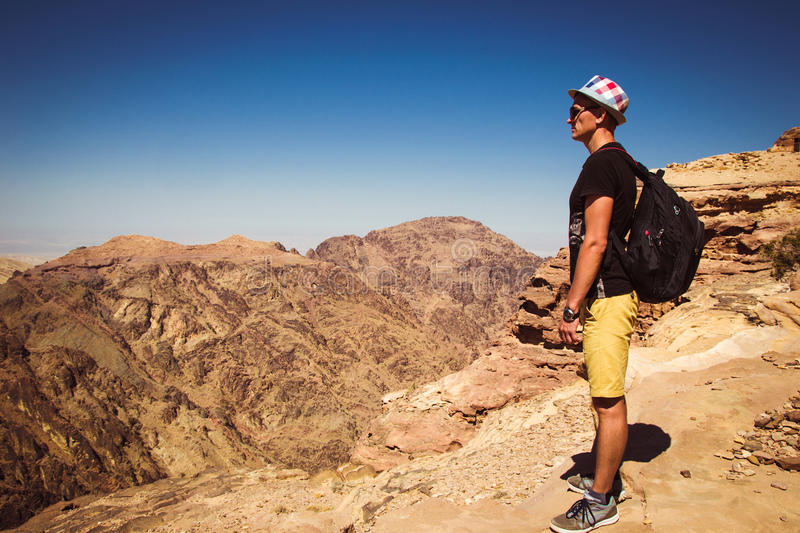 Hipster traveler contemplate impressive mountains landscape. Man with backpack and hat standing alone on top mountain enjoy freedo stock image