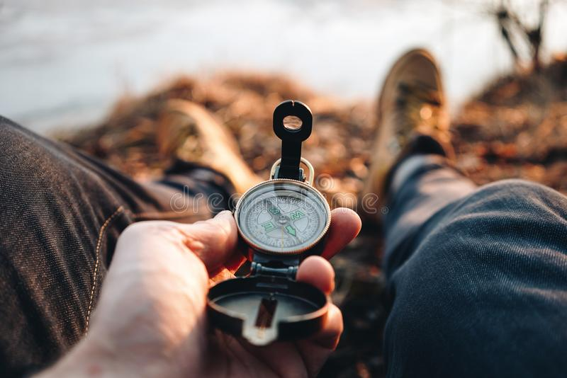 Hipster traveler hold vintage compass in hand on background of him legs in hiking boots stock photo