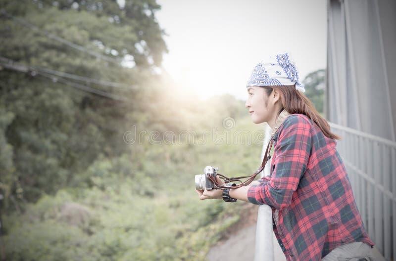 Hipster traveler woman hold vintage camera. At bridge railway stock images