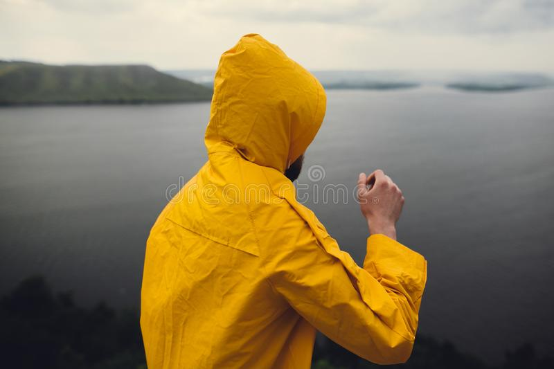 Hipster traveler in yellow raincoat standing on cliff and looking at lake in windy moody day. Wanderlust and travel concept. Man. Hiking in Norway on foggy day royalty free stock images