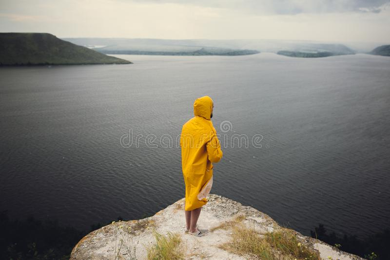 Hipster traveler in yellow raincoat standing on cliff and looking at lake in windy moody day. Wanderlust and travel concept. Man. Hiking in Norway on foggy day stock image