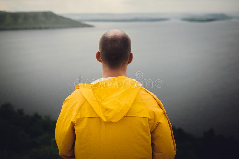 Hipster traveler in yellow raincoat standing on cliff and looking at lake in windy moody day. Wanderlust and travel concept. Man. Hiking in Norway on foggy day stock photos