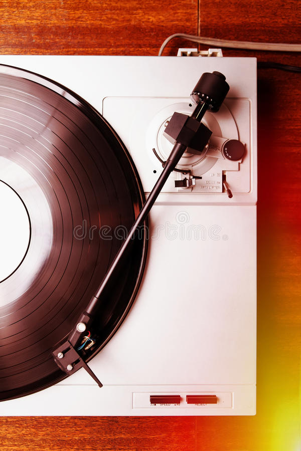 Hipster turntable playing vinyl record with music. Turntable player with musical vinyl record. Useful for DJ, nightclub and retro theme. Light leak film hipster stock photography