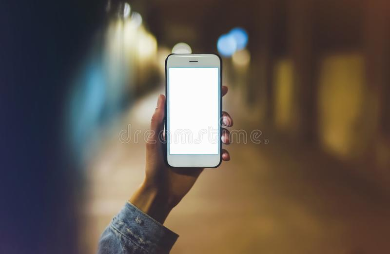 Hipster using in hands clean gadget mobile phone closeup, woman pointing finger on blank screen smartphone on background bokeh lig royalty free stock image