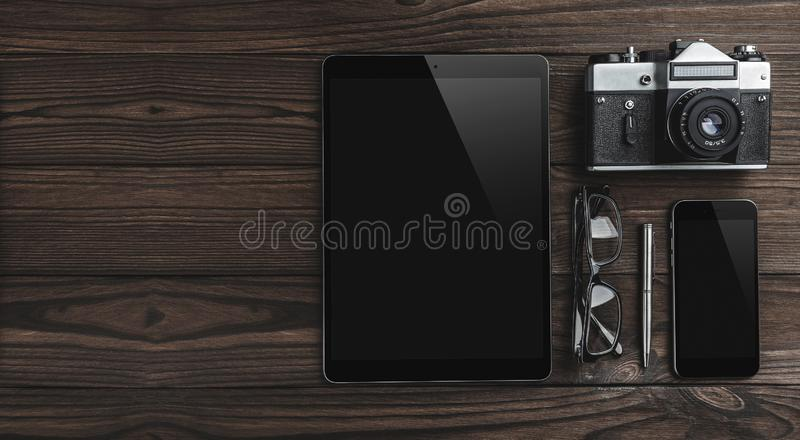 Hipster vintage wooden desktop with mobile phone, eyeglasses, pen, camera and tablet stock photography