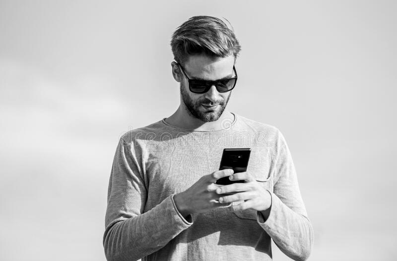 Hipster wear sunglasses hold mobile phone sky background. Hipster smartphone call. Man mobile call. Stay in touch. Mobile call concept. Important mobile stock image