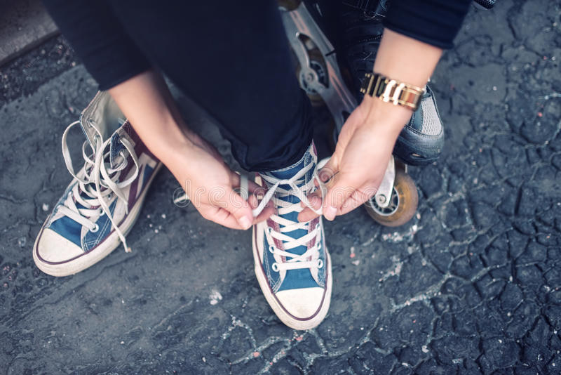 Hipster wearing sneakers, teenager tieing laces at sport shoes. Urban lifestyle with footwear and modern clothing. Hipster wearing sneakers, teenager tieing stock images