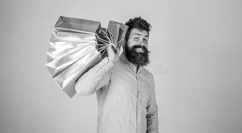 Hipster on winking face shopping. Guy shopping on sales season, carries bunch of bags on shoulder. Man with beard and. Mustache holds shopping bags, grey royalty free stock image
