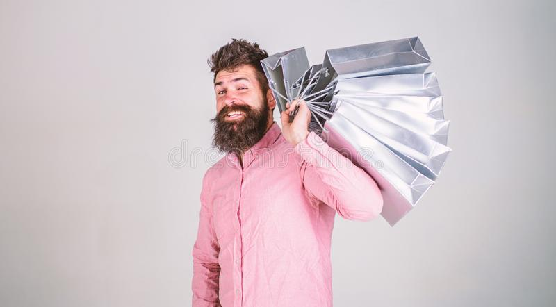 Hipster on winking face shopping. Guy shopping on sales season, carries bunch of bags on shoulder. Man with beard and. Mustache holds shopping bags, grey royalty free stock photos