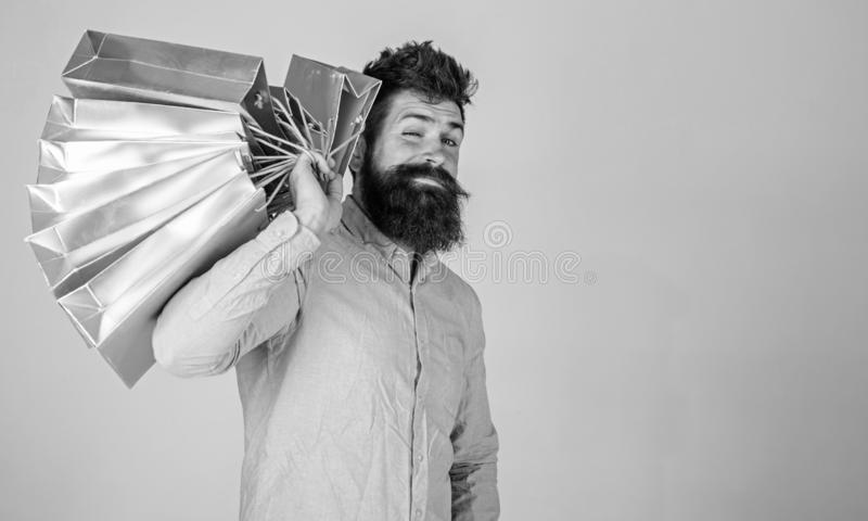 Hipster on winking face shopping. Shopping concept. Guy shopping on sales season, carries bunch of bags on shoulder. Man. With beard and mustache holds shopping royalty free stock image