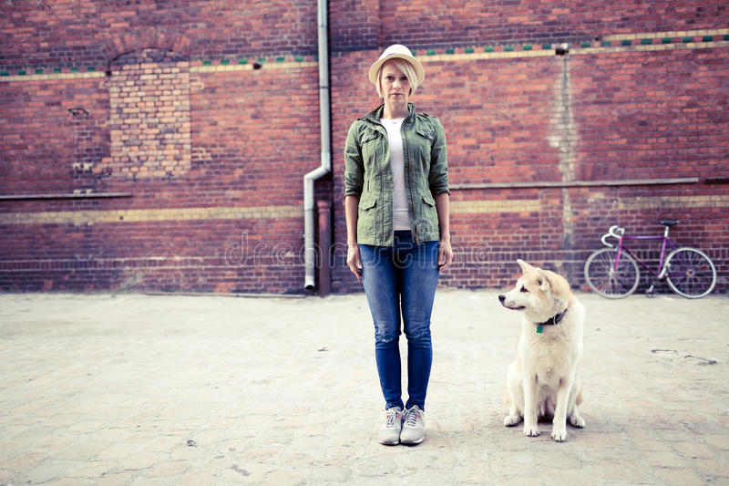 Hipster woman with dog and vintage road bike in city. Hipster young beautiful girl with vintage road bike in city and akita inu dog, looking at camera urban stock photography