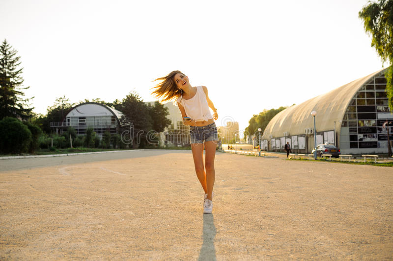 Hipster woman having fun, listening music and dancing. Outdoor summer lifestyle image of young pretty hipster woman having fun, listening music and dancing royalty free stock images