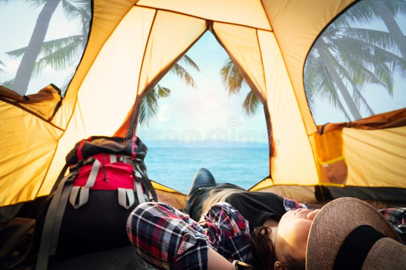 Hipster woman resting and sleeping in the tent picnic on holiday with the beautiful sea view background . stock photo
