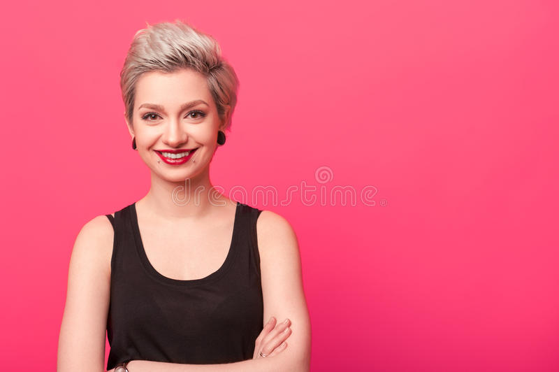 Hipster woman smiling against a pink background stock image