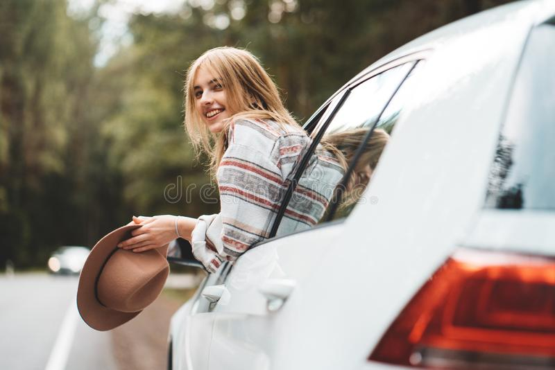 Hipster woman traveling by car on wild forest road. Handsome happy girl wearing checkered shirt and hat is sitting at the wheel of royalty free stock images