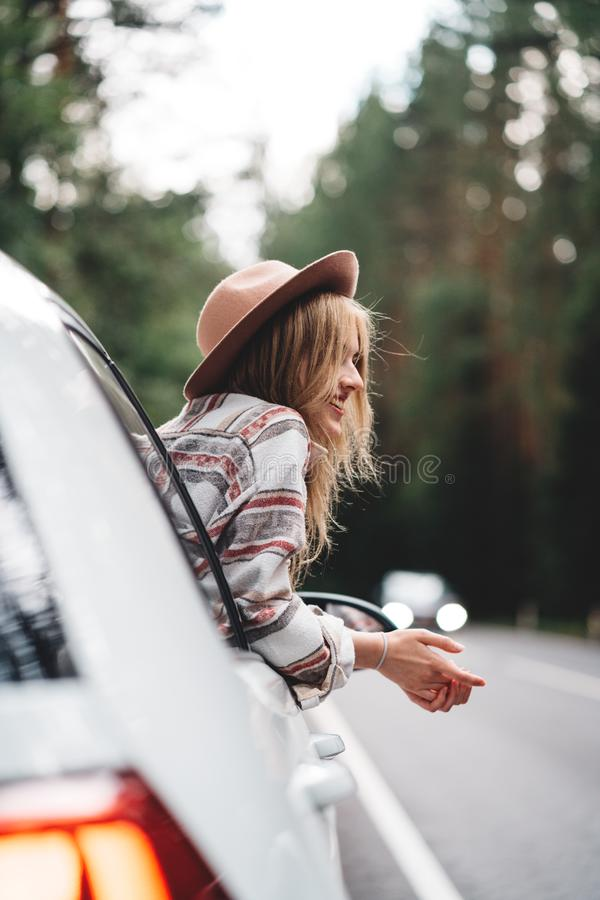 Hipster woman traveling by car on wild forest road. Handsome happy girl wearing checkered shirt and hat is sitting at the wheel of stock photo