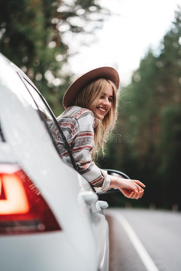 Hipster woman traveling by car on wild forest road. Handsome happy girl wearing checkered shirt and hat is sitting at the wheel of stock images