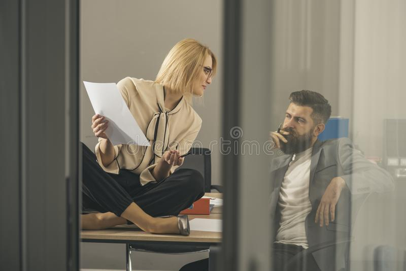 Hipster and woman work together in office, concentrated on work. Hipster and businesswoman write business plan. Hipster and women work together in office royalty free stock photography