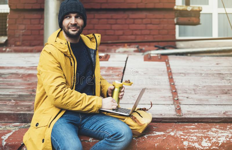Hipster with yellow backpack, jacket, cap, drink coffee of thermo cup, freelance using computer open laptop in spring street royalty free stock image