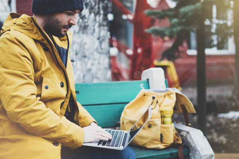 Hipster with yellow backpack, jacket, cap, thermo cup of coffee using computer open laptop in spring street outdoor, tourist man stock image