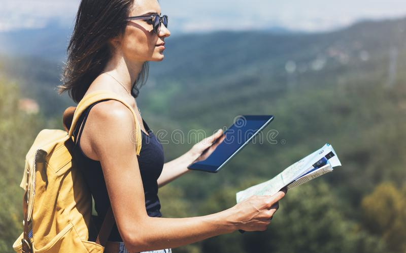 Hipster young girl with backpack enjoying panoramic mountain sea, using map and looking at horizon. Tourist traveler texting. On tablet computer on background royalty free stock photography
