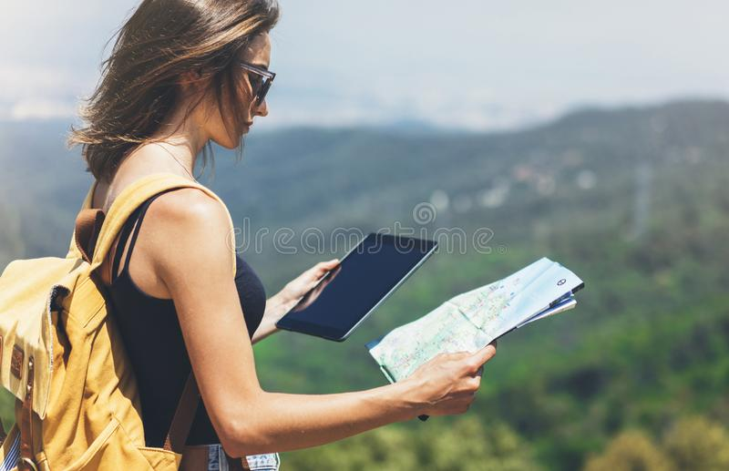 Hipster young girl with backpack enjoying panoramic mountain sea, using map and looking at horizon. Tourist traveler texting. On tablet computer on background royalty free stock image