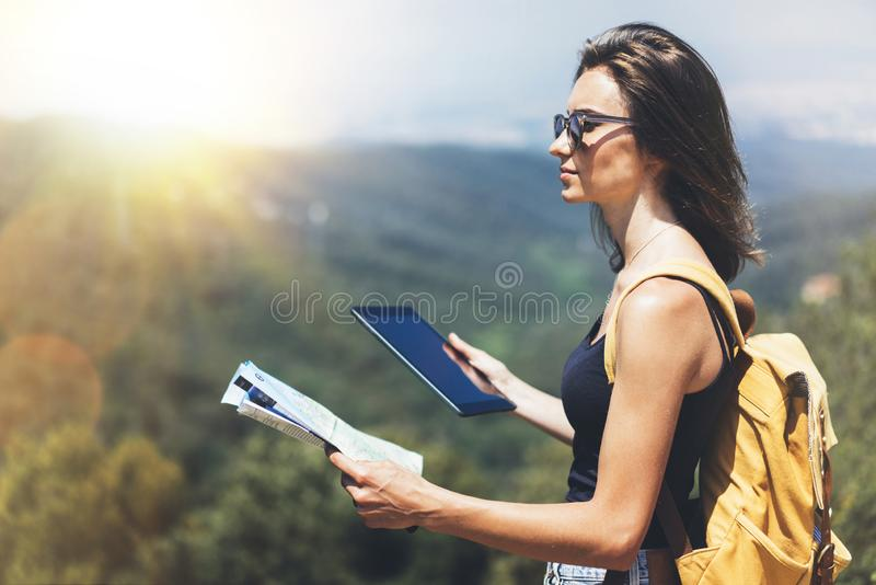 Hipster young girl with backpack enjoying panoramic mountain sun sea, using map and looking at horizon. Tourist traveler texting. On tablet computer on royalty free stock photo