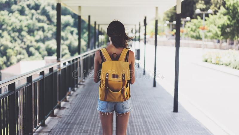Hipster young girl with backpack enjoying summer mountain. View from a back tourist traveler in short on blur background valley stock photo