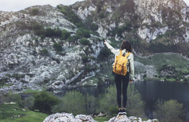 Hipster young girl with backpack enjoying sunset on peak of foggy mountain, looking on lake and poining hand. Tourist traveler royalty free stock images