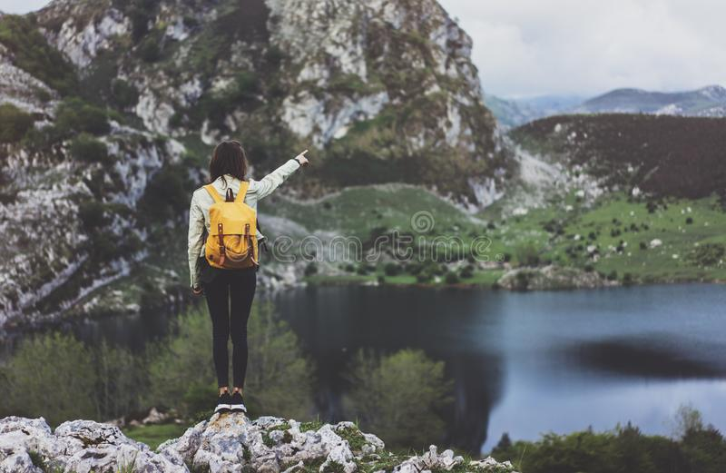 Hipster young girl with backpack enjoying sunset on peak of foggy mountain, looking on lake and poining hand. Tourist traveler. On background valley landscape stock photography